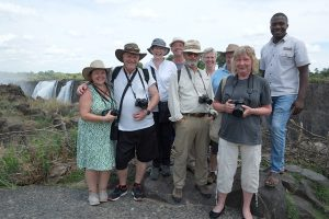 Group of travellers and their guide at Vic Falls in Zimbabwe - lodge-accommodated safari