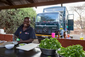 The cook preparing a meal on an overland camping safari