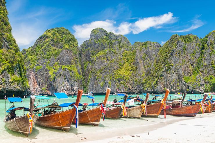 A row of long-tail boats at Maya Bay in Thailand