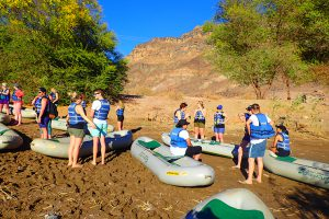 People getting ready for a canoeing trip - overland camping vs lodge-accommodated safaris
