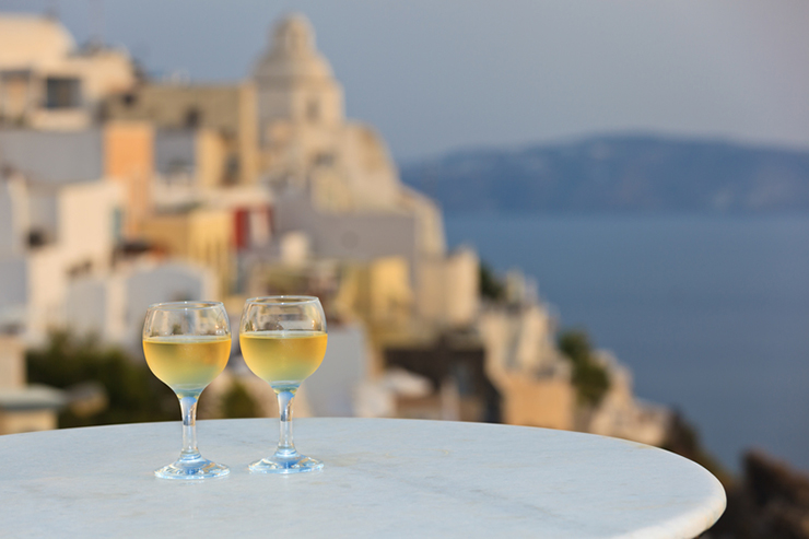 Two glasses of wine with a view of Santorini, one of the best wine tasting destinations