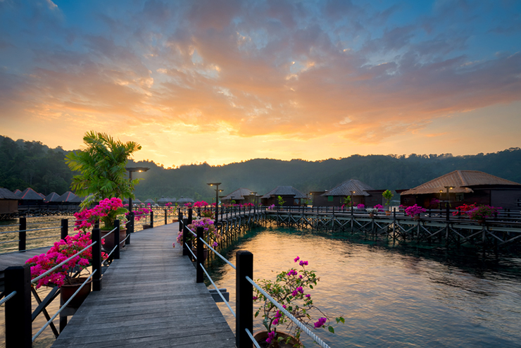 Over-water bungalows at dusk with beautiful sunset, Borneo