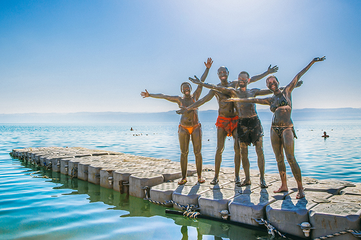 Group covered in mud at the Dead Sea, Jordan