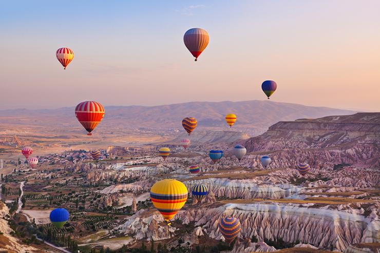 Hot air balloon flying over Cappadocia Turkey at sunrise