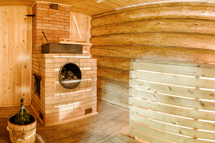 Russian wooden sauna banya with spruce broom and oven with stones