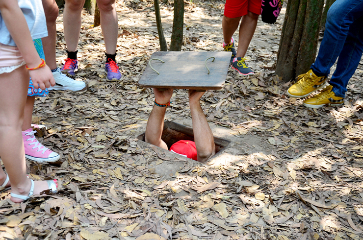 Group at a trapdor to the Cu Chi Tunnels, Vietnam