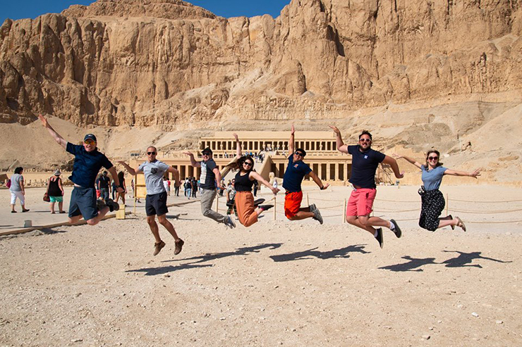Group tour jumping in front of Queen Hetsepsut's temple, Egypt