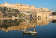 2 local men in a boat across the water from the magnificant Amber Fort