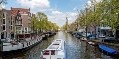A sightseeing boat makes its way along the famous canals of Amsterdam