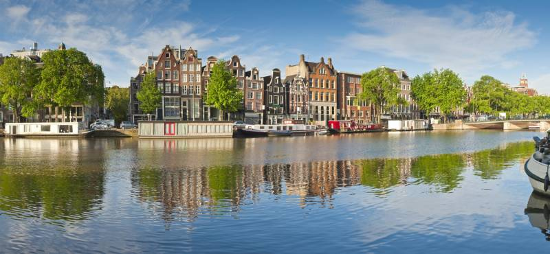 Pretty dutch doll houses reflected in the tranquil canals of Amsterdam
