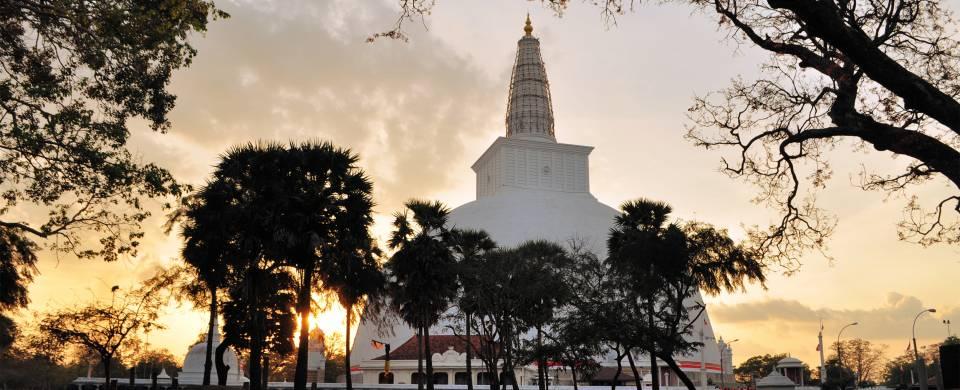 The setting sun behind a temple in Anuradhapura