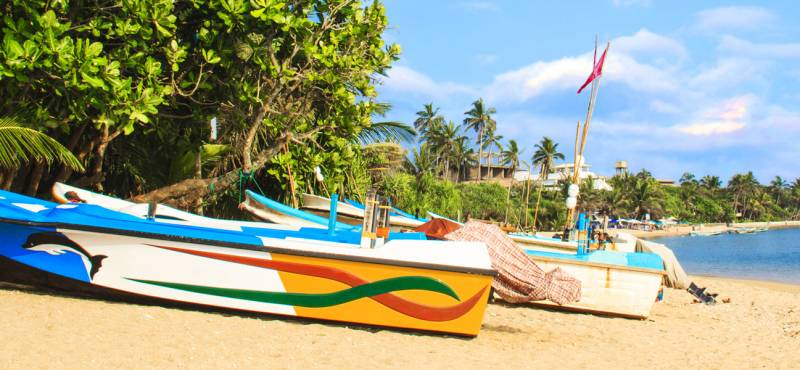 Colourful fishing boats line the sandy beaches of Bentota, Sri Lanka where we offer day tours and gu
