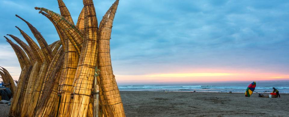 Straw boats in the sand at the beach in Chiclayo at sunset