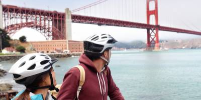 Young couple on a bike tour of San Francisco admiring the Golden Gate Bridge