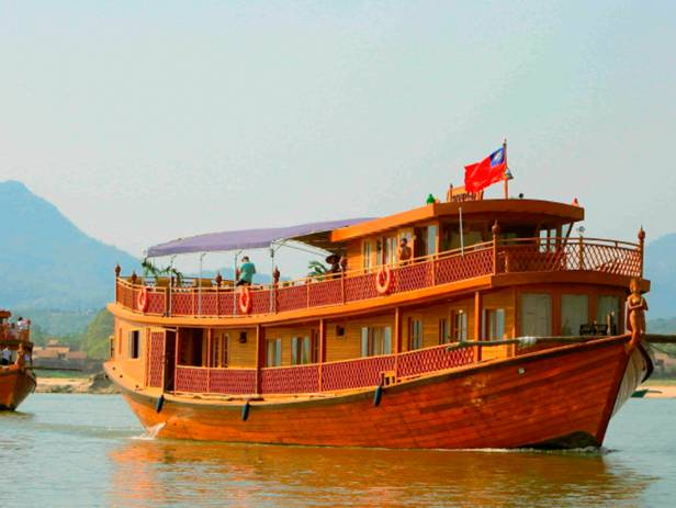 The RV Paukan cruise boat plies its course on the Irrawaddy River with Buddhist stupas as a backdrop