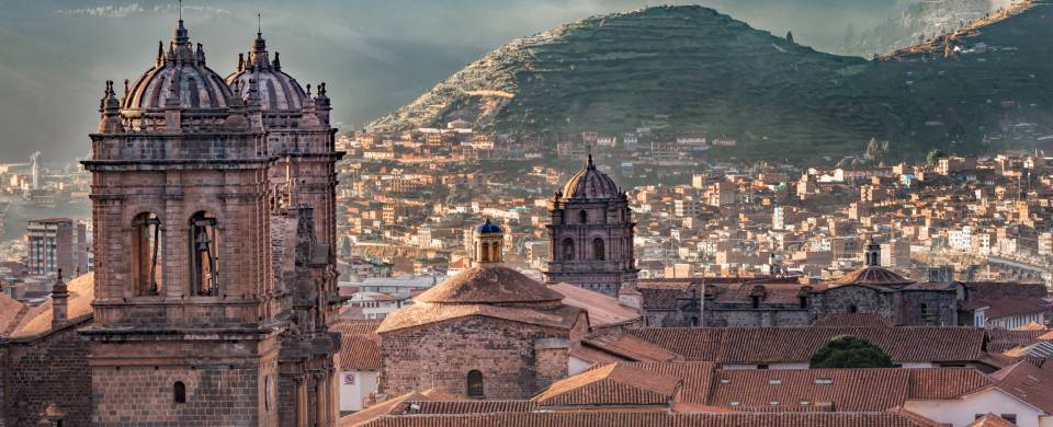 Looking out across the rooftops around the Plaza de Armas in Cuzco with the Andean mountains in the