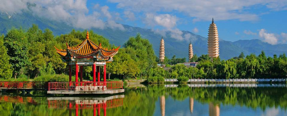 A temple of the waterfront, surrounded by lush foliage, in Dali