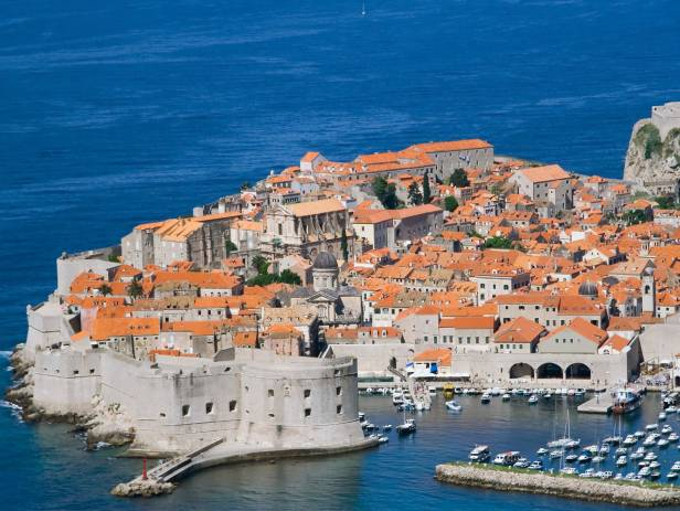 Aerial view of Dubrovnik, surrounded by water and filled with terracotta-roofed buildings