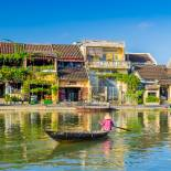 A traditional longboat sails along the river in Hoi An