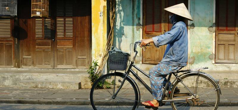 A Vietnamese lady cycling along the streets of Hoi An