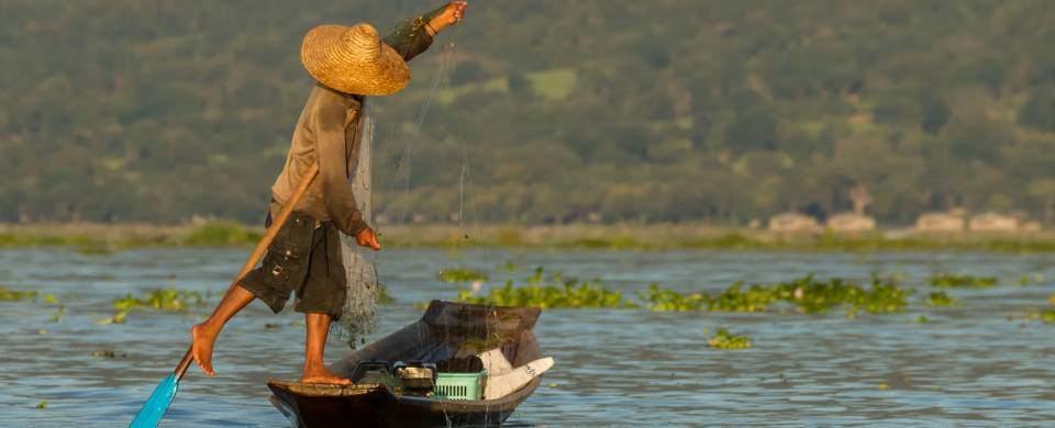 Fisherman pushing his boat in the unique style used on Inle Lake
