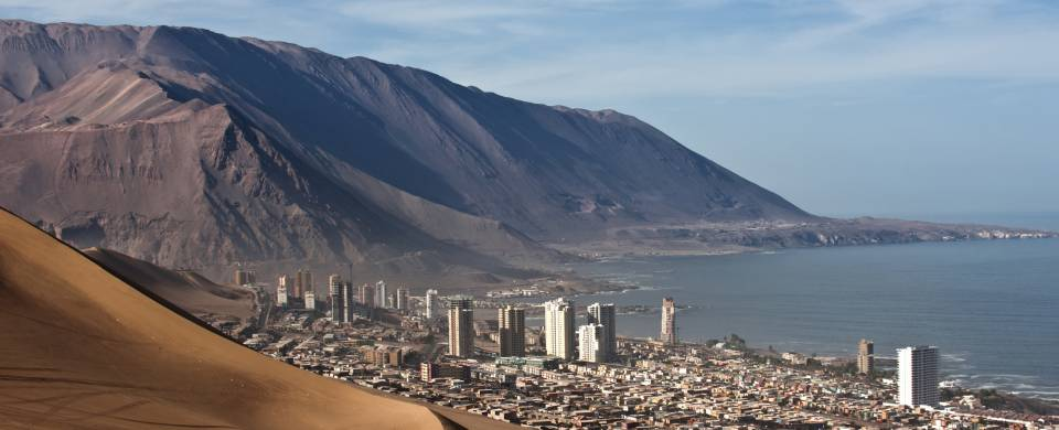 Sand dunes behind the city of Iquique and the sea in front of it