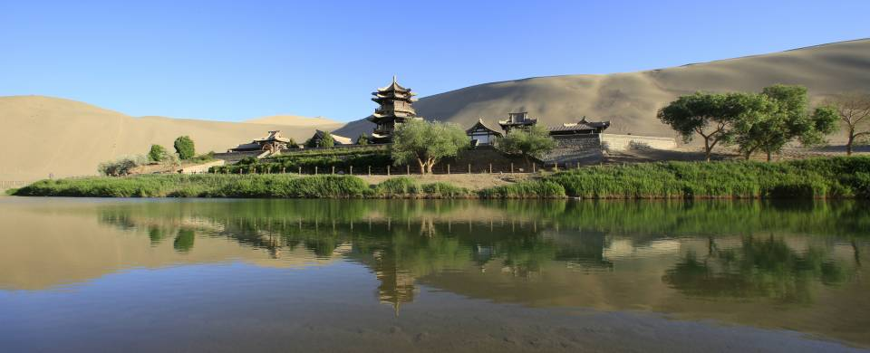 A temple standing majestically next to a lake in Jiayuguan