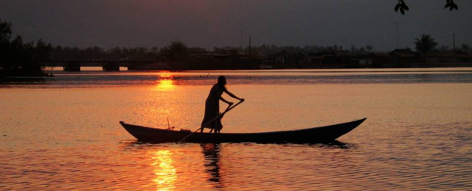 Long, thin boat being rowed across the water as the sun sets and stains the landscape orange in Kamp