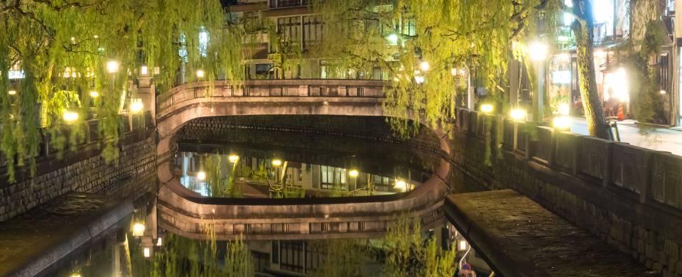 Bridge over water, lit up at night time, in Kinosaki, Onsen