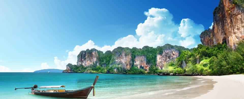 Traditional Thai boat on the crystal clear water at the beach in Krabi