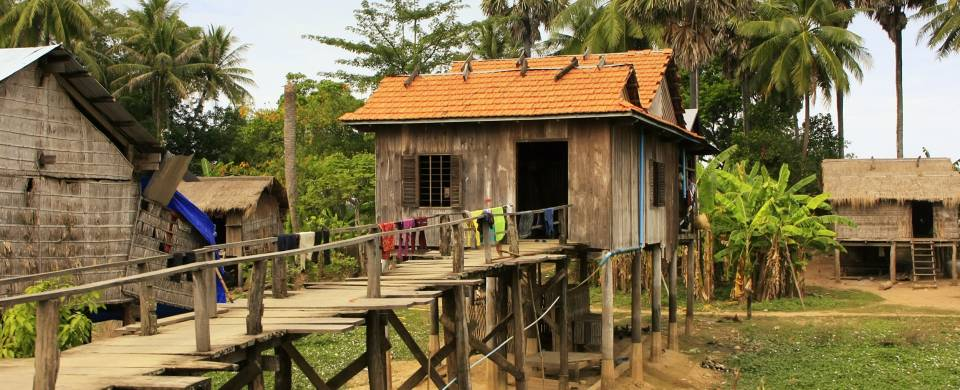 Wooden house on stilts with a rickety boardwalk in Kratie