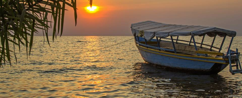 Boat on the water in front of the sunset at Lake Victoria
