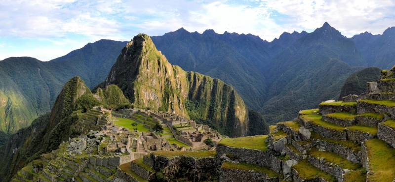 Panorama of Machu Picchu terraces, watcher's hut and Wuayna Picchu with shadow in early morning ligh