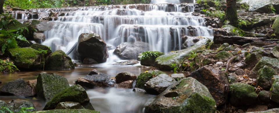 Water cascades over glistening rocks in the jungle that surrounds the village of Mae Kampong in nort