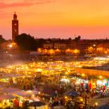 The sun begins to set over the twinkling lights of djemaa el fna square in Marrakech