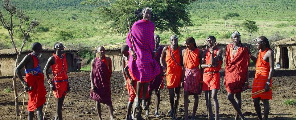 Masai Mara tribespeople standing in a row wearing colourful clothes