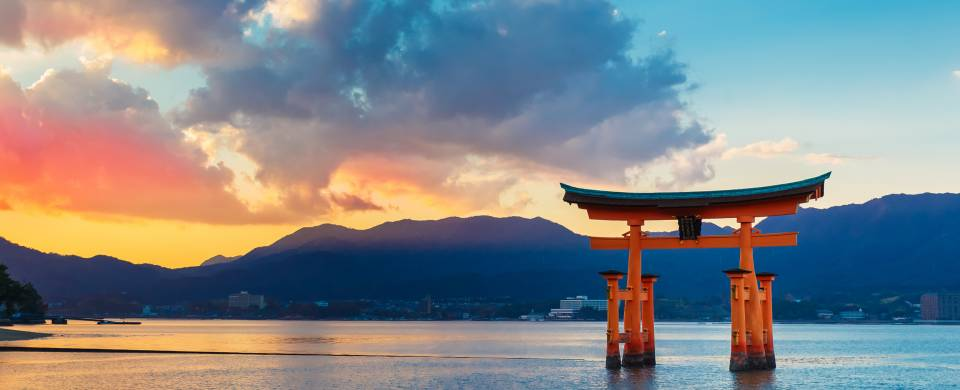 Sunset behind the iconic Miyajima monument that stands in the water