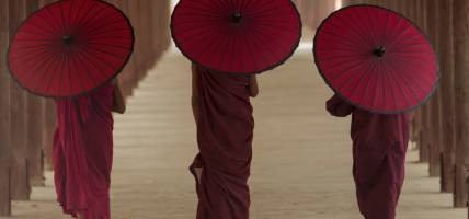 Monks walking with parasols in Myanmar - Southeast Asia - On The Go Tours