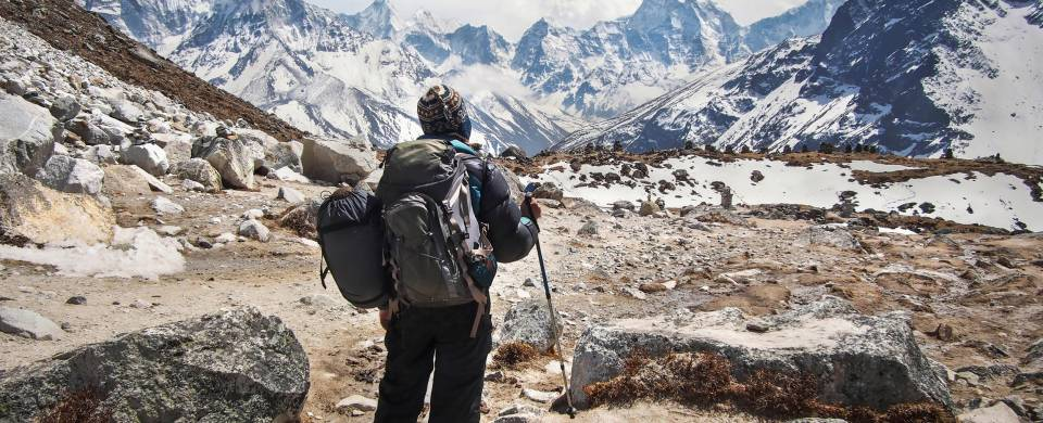 Hiker at Mount Everest Base Camp, looking at the snow-capped peaks of the Himalayas