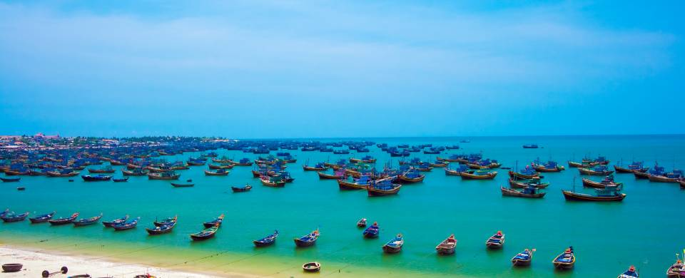 Hundreds of fishing boats floating on the turquoise water in Mui Ne