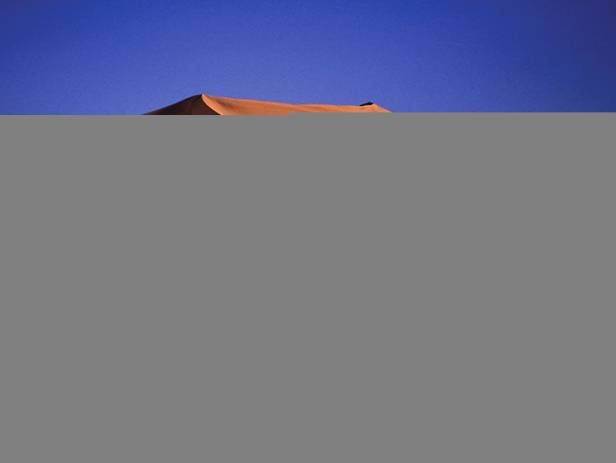 Orange sand dunes and rocky mountains at Namib Naukluft National Park