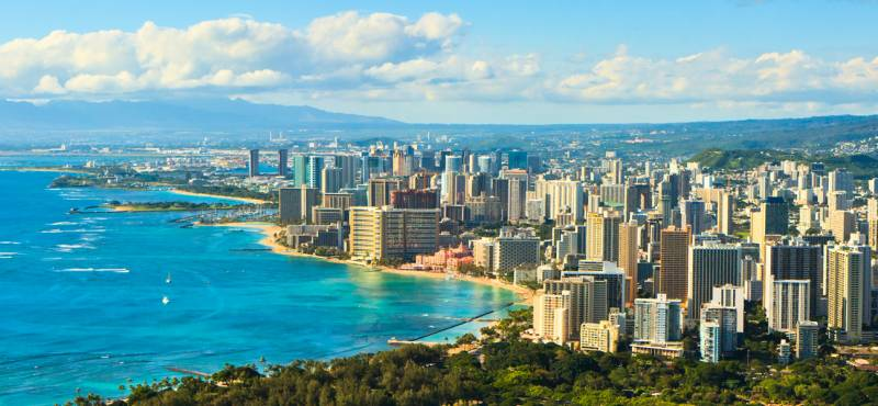 A panoramic view of the coastline of Oahu with skyscrapers fronting the beach and blue waters
