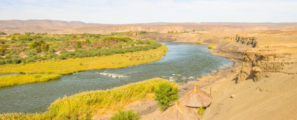 Stretch of the Orange River fringed with sandy and grassy landscape