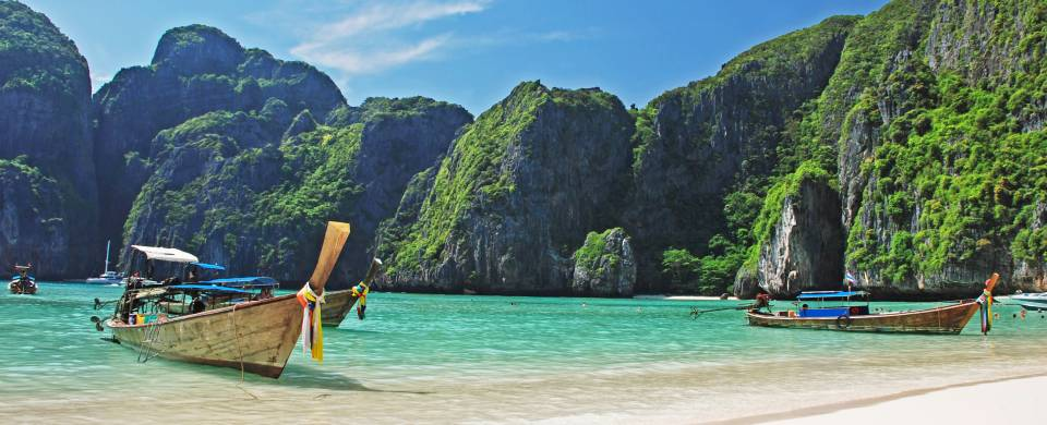 Traditional Thai boat resting on the calm ocean next to perfect white sand on Phi Phi Island