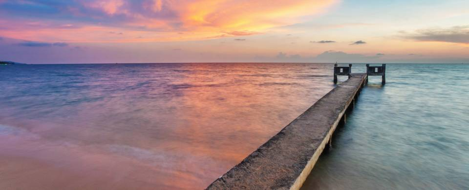 Stunning sunset, staining the sky all colours of the rainbow over a boardwalk stretching out in to t