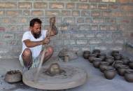 A potter gets to work on his spinning wheel in Bishnoi village