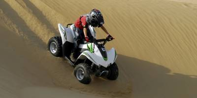 Young boy riding his quad bike in the desert