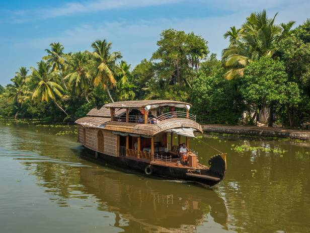 Boat sailing along the river, fringed with thick jungle, in Alleppey