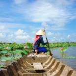 A Vietnamese woman rowing a boat in the lily-strewn waters of the Mekong Delta