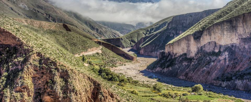 Winding road cutting through the rugged and rocky valley in Salta